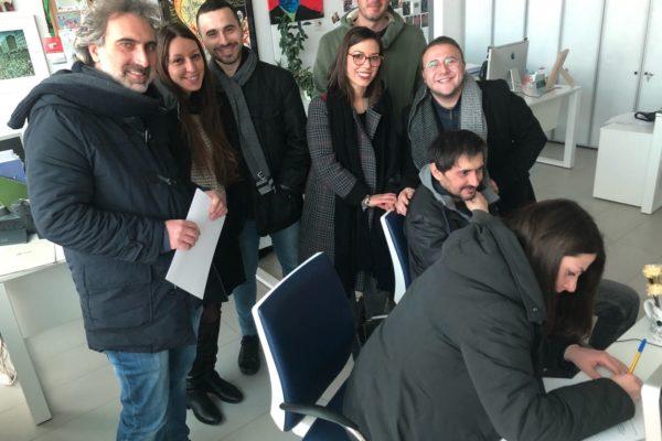otto persone in piedi e sorridenti, un anell'atto di firmare un foglio