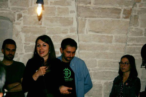 interno, persona che parla con un microfono in mano, alle spalle persone in piedi