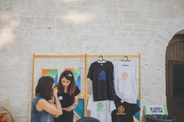 due ragazze che parlano tra loro, alle loro spalle, magliette brandizzate e gadget wonderadio