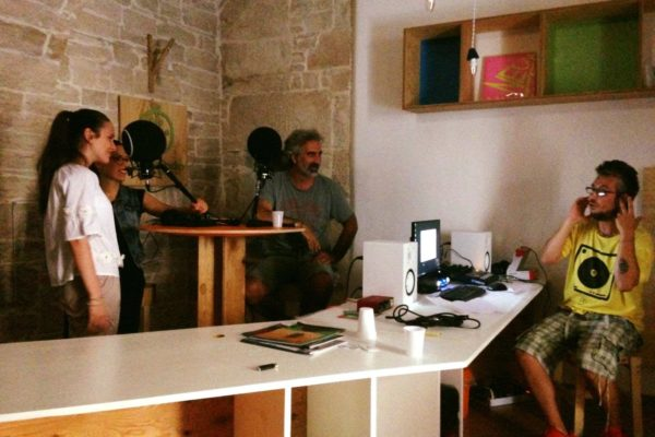 interno, due persone sedute, due in piedi,microfoni, computer e cuffie