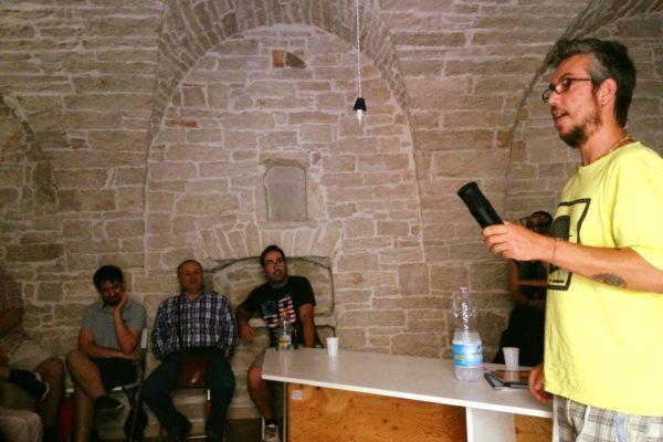 una persona in piedi con un microfono in mano, altre persone sedute in semicerchio