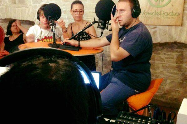 interno, testa di una persona in primo piano, sullo sfondo persone sedute ai microfoni