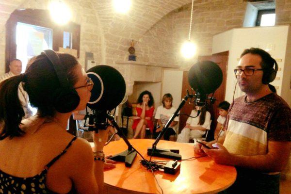 ambiente chiuso, due persone sedute ad un tavolo con due microfoni