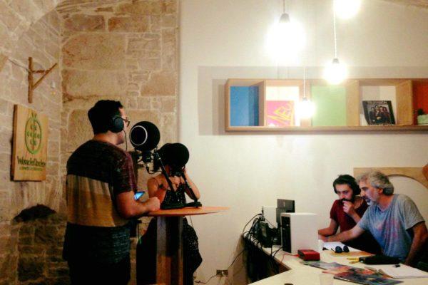 interno, due persone ai microfoni e due persone al computer