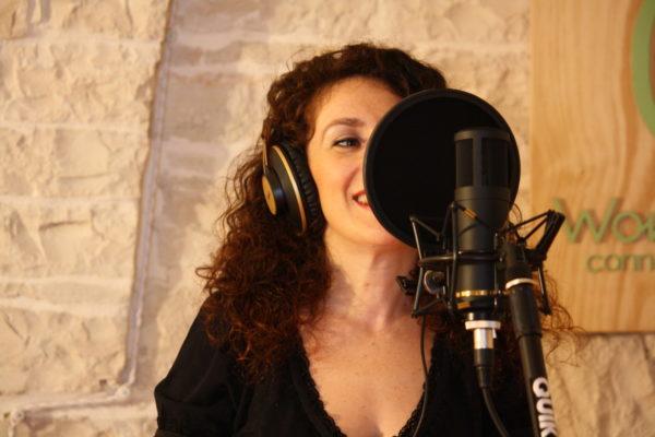 una donna sorridente con microfono e cuffie