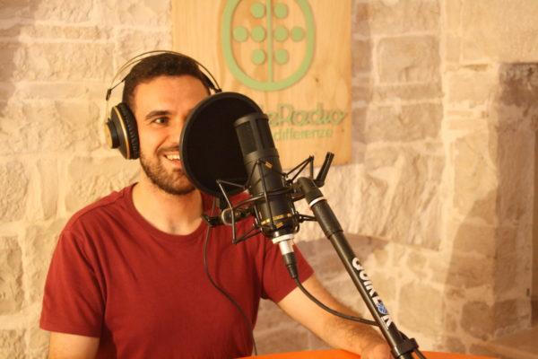 ambiente chiuso, ragazzo che sorride seduto davanti ad un microfono, con cuffie, sullo sfondo il logo di wonderadio