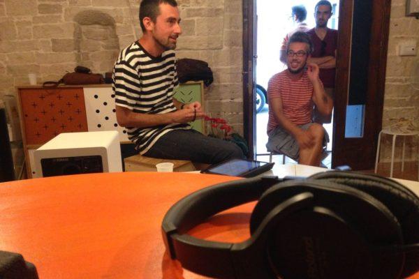 ambiente interno, una persona seduta che parla, in primo piano delle cuffie