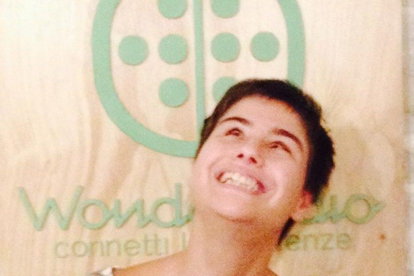ambiente interno, una persona in piedi che sorride, alle spalle il logo di wonderadio