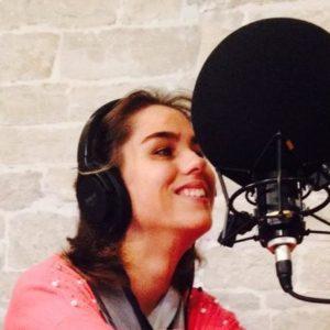 una persona sorridente con microfono e cuffie