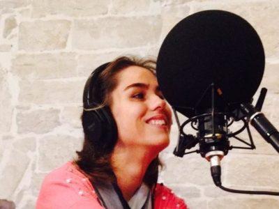 ambiente interno, una persona seduta davanti ad un microfono che sorride