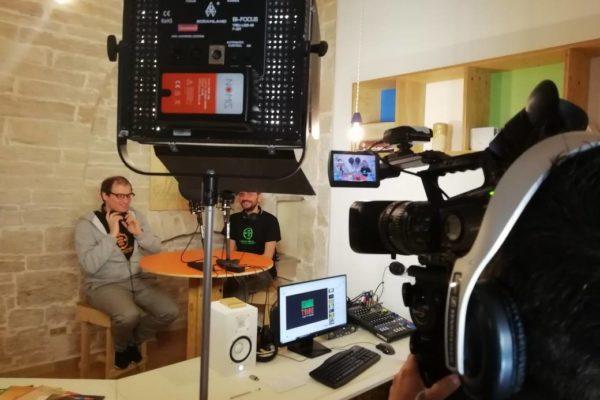 ambiente interno, strumentazione per riprese video in studio, due persone con cuffie