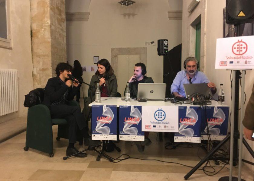 foto con tavolo speakers quattro persone sedute con microfono e cuffie