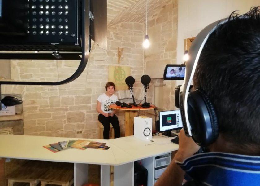 immagine di un operatore video che riprende una speaker davanti ai microfoni